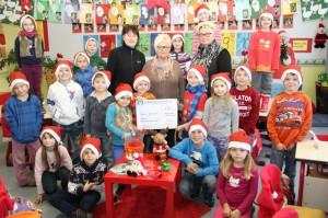 Susanne Werthen (links) und Heike Czarnyan (rechts) vom Guter Zweck e.V. nahmen gemeinsam mit den Schülerinnen und Schüler der Grundschule die Spende von Margarate Culand entgegen.